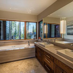 Imagen de cuarto de baño principal, rural, con puertas de armario de madera en tonos medios, bañera encastrada sin remate, paredes grises, lavabo sobreencimera, suelo gris y encimeras grises