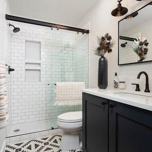 デンバーのトランジショナルスタイルのおしゃれな浴室 (シェーカースタイル扉のキャビネット、黒いキャビネット、アルコーブ型シャワー、白いタイル、サブウェイタイル、白い壁、アンダーカウンター洗面器、マルチカラーの床、引戸のシャワー、白い洗面カウンター) の写真