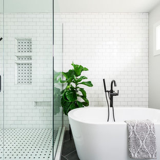 Photo of a classic ensuite bathroom in Denver with a freestanding bath, a corner shower, white tiles, metro tiles, white walls and black floors.