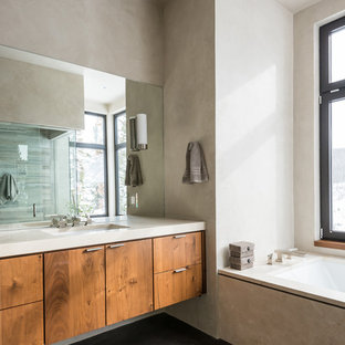 Photo of a contemporary bathroom in Other with flat-panel cabinets, dark wood cabinets, a submerged bath, grey tiles, concrete flooring and a submerged sink.