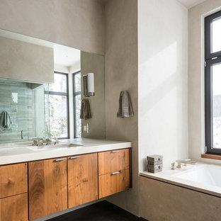 Idées déco pour une salle de bain contemporaine avec un placard à porte plane, des portes de placard en bois sombre, une baignoire encastrée, un carrelage gris, béton au sol et un lavabo encastré.