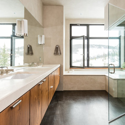 Example of a large trendy master white tile concrete floor bathroom design in Other with flat-panel cabinets, medium tone wood cabinets, beige walls, an undermount sink and solid surface countertops