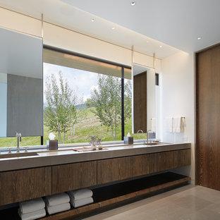 Стильный дизайн: ванная комната в современном стиле с плоскими фасадами, белой плиткой, белыми стенами, полом из известняка, монолитной раковиной, столешницей из известняка, серым полом, темными деревянными фасадами и серой столешницей - последний тренд