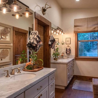 Bathroom - mid-sized rustic master medium tone wood floor and brown floor bathroom idea in Sacramento with shaker cabinets, beige cabinets, white walls, marble countertops, an undermount sink and gray countertops