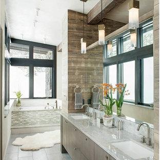Foto di una stanza da bagno padronale minimalista di medie dimensioni con ante lisce, ante grigie, pareti bianche, pavimento in gres porcellanato, pavimento grigio, vasca sottopiano, lavabo sottopiano e top in quarzite