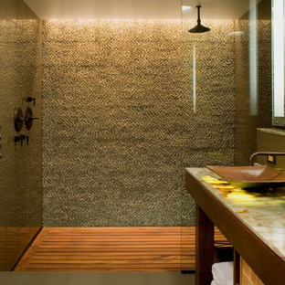 This is an example of a country bathroom in Denver with onyx benchtops and glass tile.