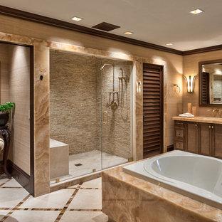 他の地域の広いトランジショナルスタイルのおしゃれなマスターバスルーム (アンダーカウンター洗面器、ドロップイン型浴槽、アルコーブ型シャワー、ベージュのタイル、シェーカースタイル扉のキャビネット、石スラブタイル、ベージュの壁、大理石の床、大理石の洗面台、中間色木目調キャビネット) の写真