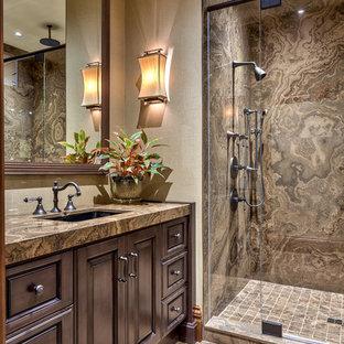 Imagen de cuarto de baño rústico con lavabo bajoencimera, armarios con paneles con relieve, puertas de armario de madera en tonos medios, ducha empotrada, baldosas y/o azulejos marrones, suelo marrón y encimeras marrones