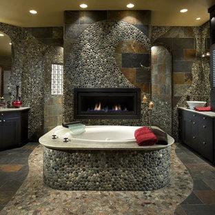 フェニックスの大きいコンテンポラリースタイルのおしゃれなマスターバスルーム (マルチカラーの壁、スレートの床、ベッセル式洗面器、フラットパネル扉のキャビネット、濃色木目調キャビネット、ドロップイン型浴槽、マルチカラーのタイル、石タイル、人工大理石カウンター) の写真