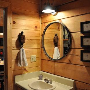 Foto de cuarto de baño con ducha, rústico, pequeño, con armarios con paneles lisos, puertas de armario de madera clara, bañera empotrada, combinación de ducha y bañera, sanitario de dos piezas, suelo de madera clara, lavabo encastrado y encimera de laminado