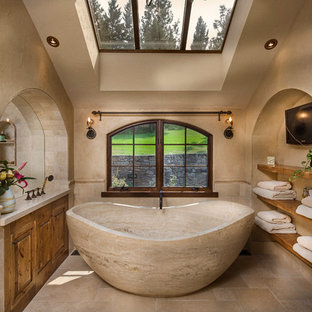 Photo of a large mediterranean ensuite bathroom in Other with raised-panel cabinets, medium wood cabinets, beige tiles, stone tiles, a freestanding bath, beige walls, limestone flooring and beige floors.