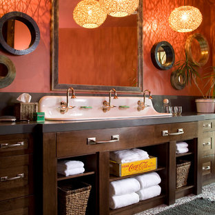 Imagen de cuarto de baño rural con lavabo de seno grande, puertas de armario de madera en tonos medios, parades naranjas, armarios estilo shaker y encimeras grises