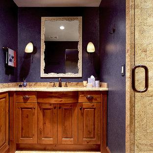 Ejemplo de cuarto de baño con ducha, rústico, de tamaño medio, con armarios con paneles con relieve, puertas de armario de madera oscura, ducha empotrada, baldosas y/o azulejos beige, baldosas y/o azulejos de piedra, paredes púrpuras, suelo de piedra caliza, lavabo bajoencimera, encimera de granito, suelo beige y ducha con puerta con bisagras
