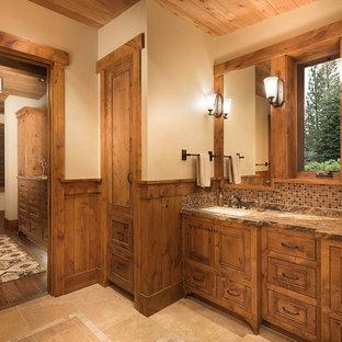 Modelo de cuarto de baño principal, rústico, de tamaño medio, con armarios con paneles empotrados, puertas de armario de madera oscura, bañera empotrada, ducha empotrada, baldosas y/o azulejos marrones, baldosas y/o azulejos en mosaico, paredes beige, suelo de madera oscura, lavabo sobreencimera y encimera de granito