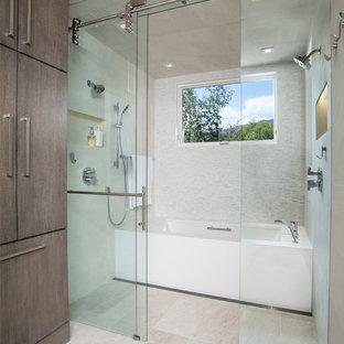 Пример оригинального дизайна: большая главная ванная комната в современном стиле с плоскими фасадами, душем без бортиков, монолитной раковиной, фасадами цвета дерева среднего тона, раздельным унитазом, белой плиткой, удлиненной плиткой, белыми стенами, ванной в нише, полом из известняка, бежевым полом и душем с раздвижными дверями