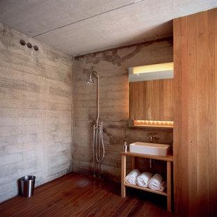 Foto di una grande stanza da bagno stile rurale con lavabo a consolle, ante in legno chiaro, top in legno, doccia aperta, WC sospeso, piastrelle grigie, piastrelle di cemento, pareti grigie, parquet scuro, doccia aperta e top marrone