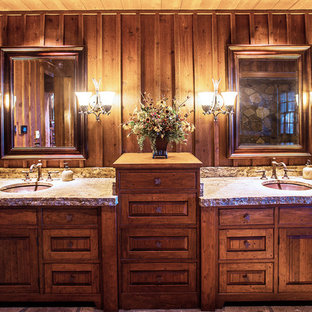 Mid-sized mountain style master travertine floor bathroom photo in Other with an undermount sink, recessed-panel cabinets, medium tone wood cabinets, granite countertops and brown walls