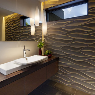 Contemporary bathroom in San Francisco with a vessel sink, flat-panel cabinets, dark wood cabinets, wooden worktops, grey tiles, white walls and brown worktops.