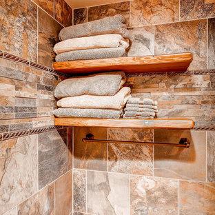 Пример оригинального дизайна: большая главная ванная комната в стиле рустика с накладной раковиной, фасадами с выступающей филенкой, фасадами цвета дерева среднего тона, столешницей из гранита, двойным душем, раздельным унитазом, бежевой плиткой, керамической плиткой, коричневыми стенами и полом из керамической плитки