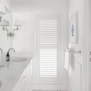 Inspiration för ett mellanstort maritimt vit vitt en-suite badrum, med skåp i shakerstil, vita skåp, ett fristående badkar, vit kakel, keramikplattor, vita väggar, klinkergolv i keramik, ett undermonterad handfat, bänkskiva i kvarts och grått golv