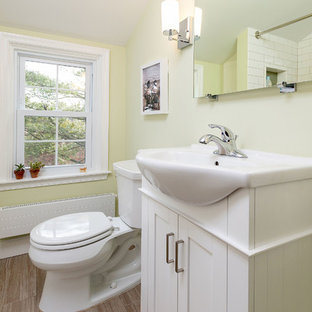 Small transitional 3/4 white tile and subway tile brown floor and porcelain floor bathroom photo in Philadelphia with shaker cabinets, white cabinets, a two-piece toilet, yellow walls, a console sink, quartz countertops and white countertops