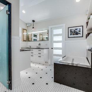 Diseño de cuarto de baño principal, actual, grande, con armarios con paneles lisos, puertas de armario blancas, bañera esquinera, baldosas y/o azulejos blancas y negros, baldosas y/o azulejos de porcelana, paredes multicolor, suelo de baldosas de porcelana, lavabo bajoencimera, encimera de cuarzo compacto y ducha a ras de suelo