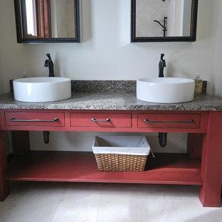 Imagen de cuarto de baño principal, de estilo americano, de tamaño medio, con lavabo sobreencimera, armarios abiertos, puertas de armario rojas, encimera de granito, paredes blancas y suelo de terrazo