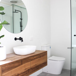This is an example of a large contemporary 3/4 bathroom in Perth with furniture-like cabinets, medium wood cabinets, a freestanding tub, a corner shower, a one-piece toilet, white tile, subway tile, white walls, porcelain floors, a vessel sink, wood benchtops, grey floor, a hinged shower door, multi-coloured benchtops, a single vanity and a floating vanity.