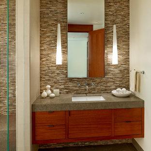 Immagine di una stanza da bagno design di medie dimensioni con lavabo sottopiano, ante lisce, ante in legno scuro, top in pietra calcarea, WC monopezzo, piastrelle multicolore, piastrelle di vetro, pareti beige e pavimento in pietra calcarea