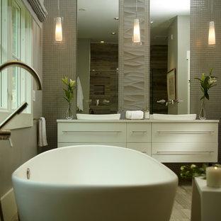 Modelo de cuarto de baño principal, contemporáneo, extra grande, con lavabo encastrado, armarios con paneles lisos, puertas de armario blancas, encimera de cuarzo compacto, bañera exenta, ducha doble, sanitario de una pieza, baldosas y/o azulejos grises, paredes grises y baldosas y/o azulejos de piedra