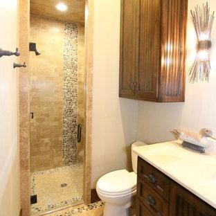 Immagine di una stanza da bagno stile rurale di medie dimensioni con ante a persiana, ante in legno bruno, doccia alcova, WC monopezzo, piastrelle di ciottoli, pareti bianche, pavimento in travertino e lavabo sottopiano