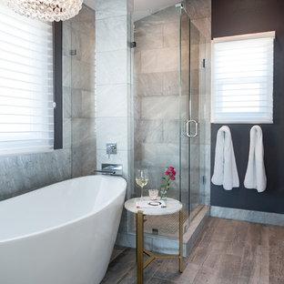 Inredning av ett klassiskt mellanstort grå grått en-suite badrum, med dusch med gångjärnsdörr, ett fristående badkar, en öppen dusch, grå kakel, marmorkakel, svarta väggar, klinkergolv i porslin, marmorbänkskiva och grått golv