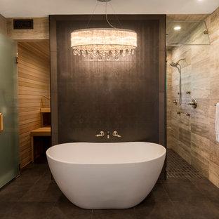 Esempio di una stanza da bagno padronale design con vasca freestanding, doccia a filo pavimento, piastrelle beige, piastrelle in pietra e porta doccia a battente