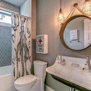 Modelo de cuarto de baño infantil, de estilo de casa de campo, de tamaño medio, con bañera encastrada, sanitario de una pieza, baldosas y/o azulejos grises, baldosas y/o azulejos de vidrio, paredes grises, suelo laminado, lavabo suspendido, suelo gris y ducha con cortina