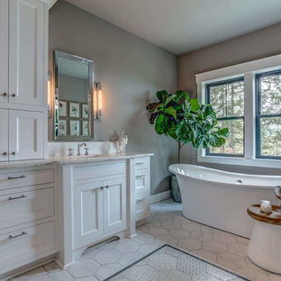 Inspiration for a large country master bathroom in Other with recessed-panel cabinets, white cabinets, a freestanding tub, a corner shower, a one-piece toilet, white tile, ceramic tile, grey walls, ceramic floors, an undermount sink, engineered quartz benchtops, white floor and a hinged shower door.
