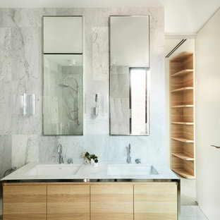 This is an example of a modern master bathroom in Sydney with flat-panel cabinets, medium wood cabinets, white tile, white walls, an undermount sink, white floor and white benchtops.