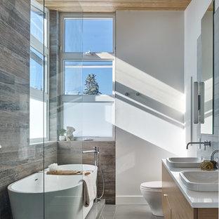 Idéer för mellanstora funkis vitt en-suite badrum, med släta luckor, skåp i ljust trä, ett fristående badkar, en öppen dusch, grå kakel, keramikplattor, vita väggar, klinkergolv i porslin, ett fristående handfat, bänkskiva i kvarts, grått golv och med dusch som är öppen