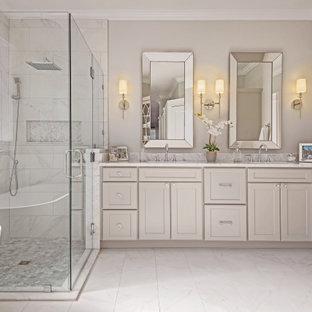 Aménagement d'une grand salle de bain principale classique avec un placard à porte plane, des portes de placard beiges, un bain bouillonnant, une douche d'angle, un WC à poser, un carrelage gris, du carrelage en marbre, un mur beige, un sol en marbre, un lavabo encastré, un plan de toilette en quartz modifié, un sol blanc, une cabine de douche à porte coulissante, un plan de toilette blanc, une niche, meuble double vasque et meuble-lavabo encastré.