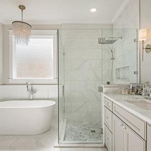 Bild på ett stort vintage vit vitt en-suite badrum, med släta luckor, beige skåp, en jacuzzi, en hörndusch, en toalettstol med hel cisternkåpa, grå kakel, marmorkakel, beige väggar, marmorgolv, ett undermonterad handfat, bänkskiva i kvarts, vitt golv och dusch med skjutdörr