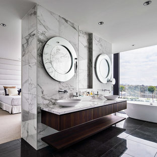 Inspiration for a large contemporary master bathroom in Melbourne with dark wood cabinets, a freestanding tub, white tile, marble, white walls, porcelain floors, marble benchtops, white benchtops, flat-panel cabinets, a vessel sink and black floor.