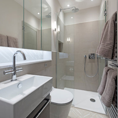 Example of a small ornate master beige tile and porcelain tile porcelain tile and multicolored floor walk-in shower design in London with flat-panel cabinets, a wall-mount toilet, white walls, a wall-mount sink, quartz countertops and a hinged shower door