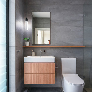 Inspiration for a mid-sized contemporary 3/4 bathroom in Sydney with flat-panel cabinets, medium wood cabinets, gray tile, ceramic tile, ceramic floors, grey floor, an open shower, a curbless shower, a two-piece toilet and a console sink.