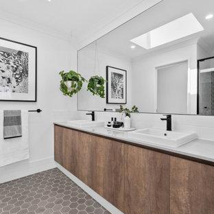 Foto di una grande stanza da bagno con doccia scandinava con ante lisce, ante in legno scuro, doccia alcova, pareti bianche, lavabo da incasso, pavimento grigio, porta doccia scorrevole e top grigio