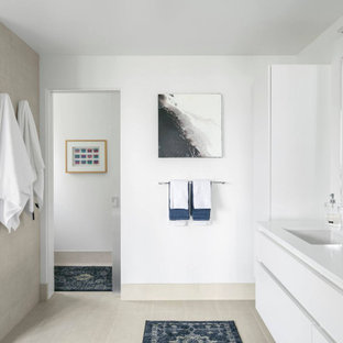Example of a minimalist beige floor and double-sink toilet room design in Seattle with flat-panel cabinets, white cabinets, white walls, an undermount sink, white countertops and a floating vanity