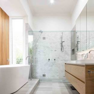 This is an example of a contemporary master bathroom in Melbourne with light wood cabinets, marble, white walls, cement tiles, engineered quartz benchtops, grey floor, flat-panel cabinets, a freestanding tub, a curbless shower, gray tile, a vessel sink, a hinged shower door and white benchtops.