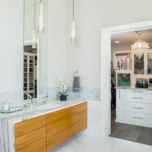Imagen de cuarto de baño principal, actual, con armarios con paneles lisos, puertas de armario de madera oscura, encimera de mármol, baldosas y/o azulejos blancos, lavabo bajoencimera y paredes grises