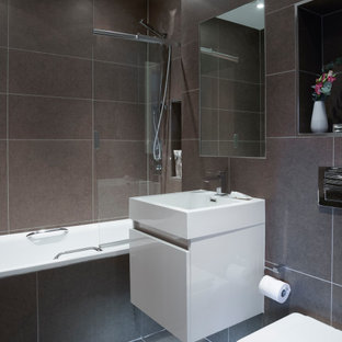 Design ideas for a small modern family bathroom in London with flat-panel cabinets, white cabinets, an alcove bath, a shower/bath combination, a one-piece toilet, brown tiles, ceramic tiles, brown walls, ceramic flooring, engineered stone worktops, brown floors and white worktops.
