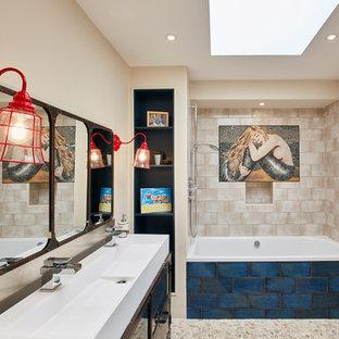 Medium sized nautical ensuite bathroom in London with an alcove bath, a shower/bath combination, beige tiles, beige walls, pebble tile flooring, a trough sink, beige floors and an open shower.