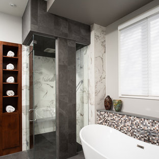 Large minimalist master gray tile and porcelain tile porcelain floor and gray floor bathroom photo in Indianapolis with flat-panel cabinets, dark wood cabinets, a one-piece toilet, white walls, an undermount sink, quartz countertops, a hinged shower door and gray countertops