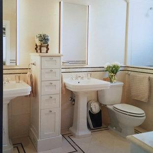 Esempio di una stanza da bagno padronale vittoriana di medie dimensioni con ante con riquadro incassato, ante bianche, vasca da incasso, vasca/doccia, WC a due pezzi, piastrelle beige, piastrelle in pietra, top in marmo e lavabo a colonna